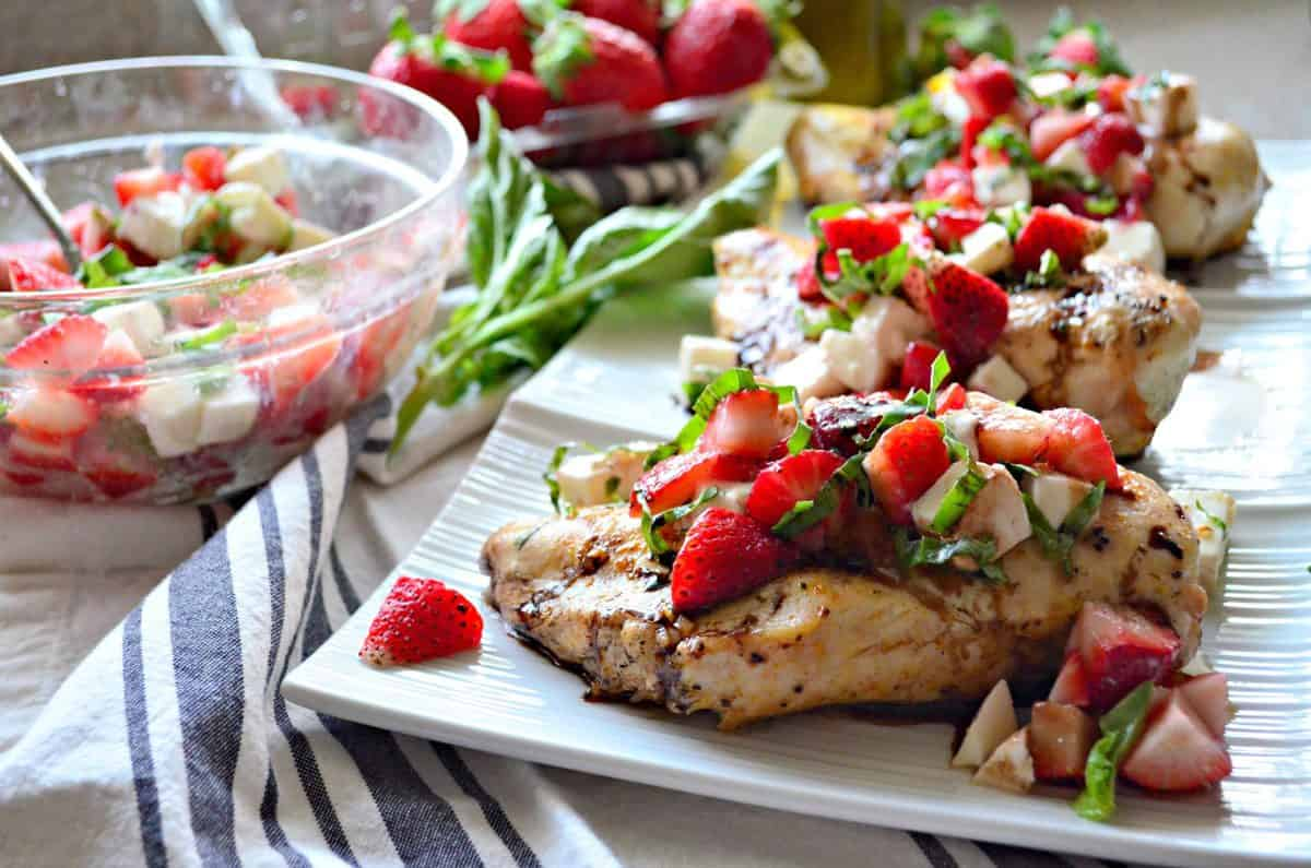 grilled chicken topped with basil, strawberries, and balsamic sauce on platter next to bowl of ingredients mixed.
