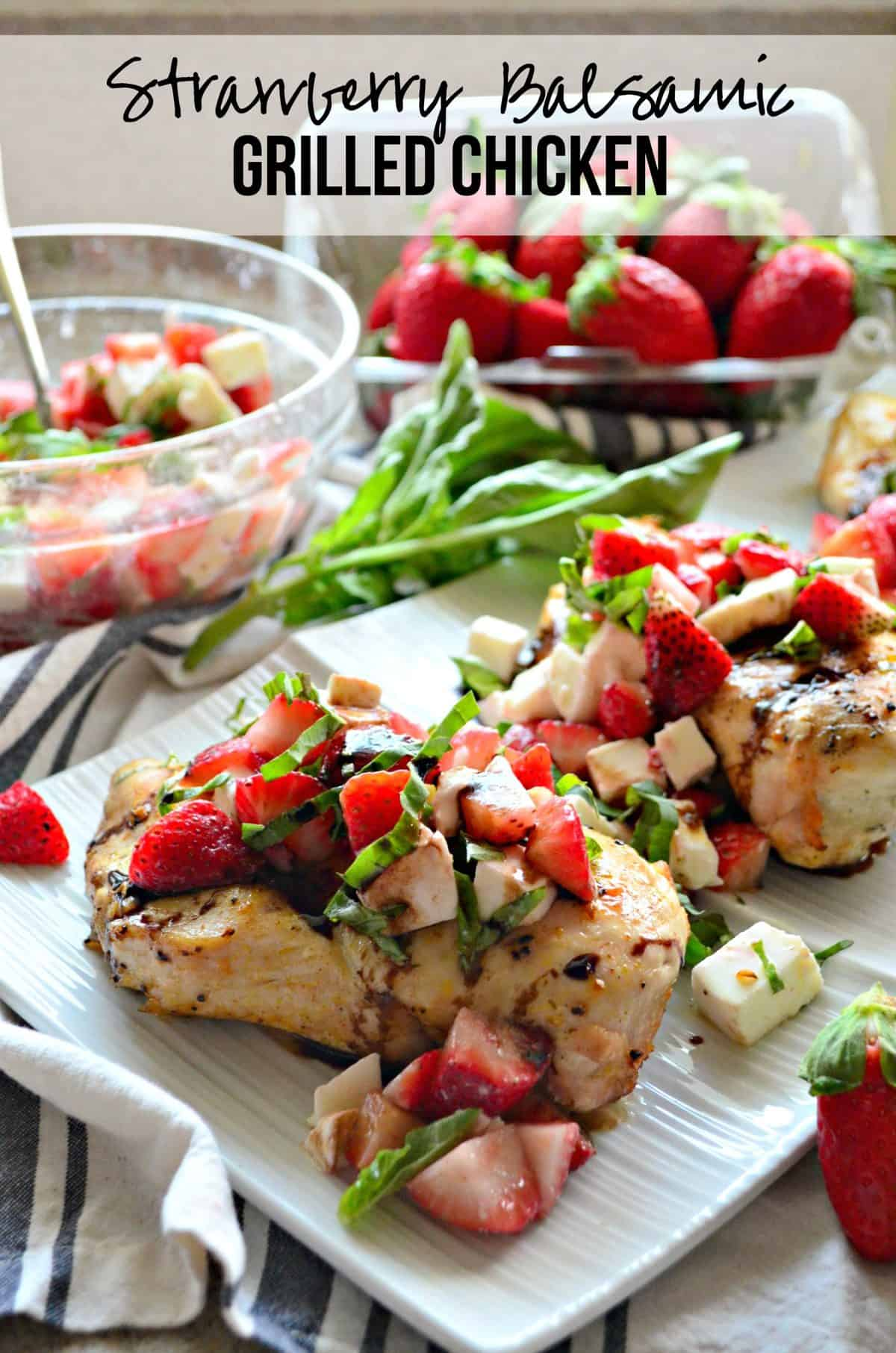 closeup grilled chicken topped with basil, strawberries, and balsamic sauce on white platter with text.