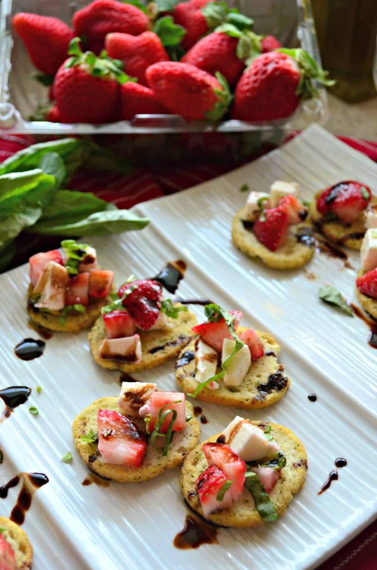closeup of herbed crackers topped with strawberries, cheese, balsamic, and basil on white platter.