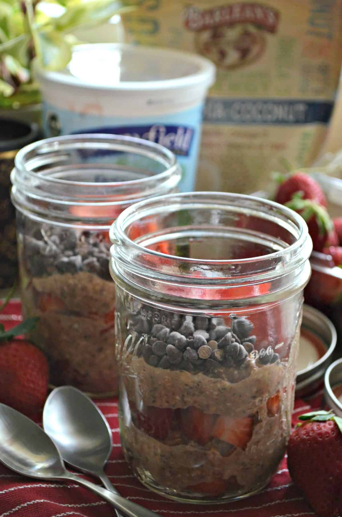 2 glass jars of layered oats, chocolate chips, and sliced strawberries with yogurt container in background.