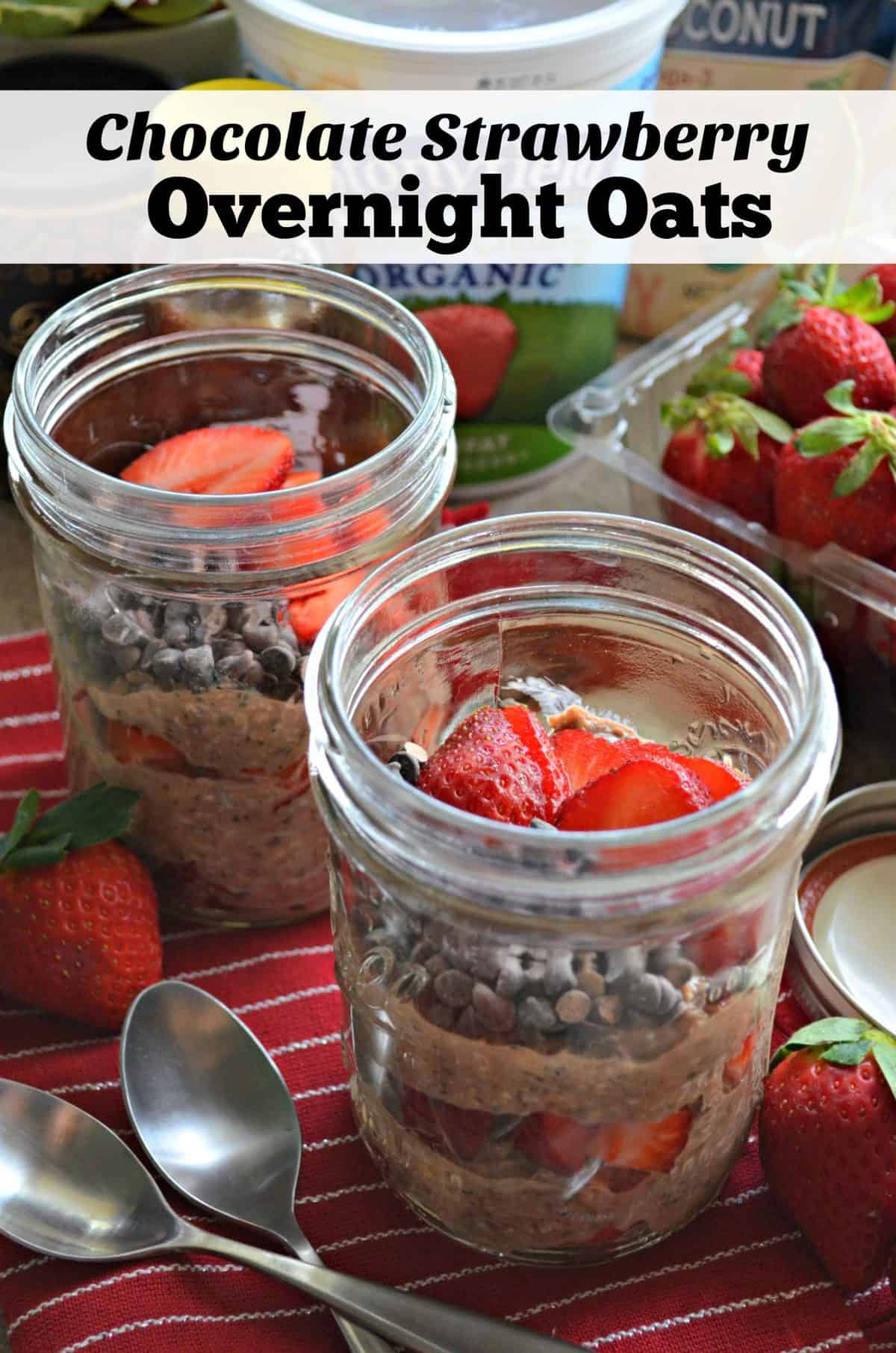 2 glass jars of layered oats, chocolate chips, and sliced strawberries on red tablecloth with strawberries.