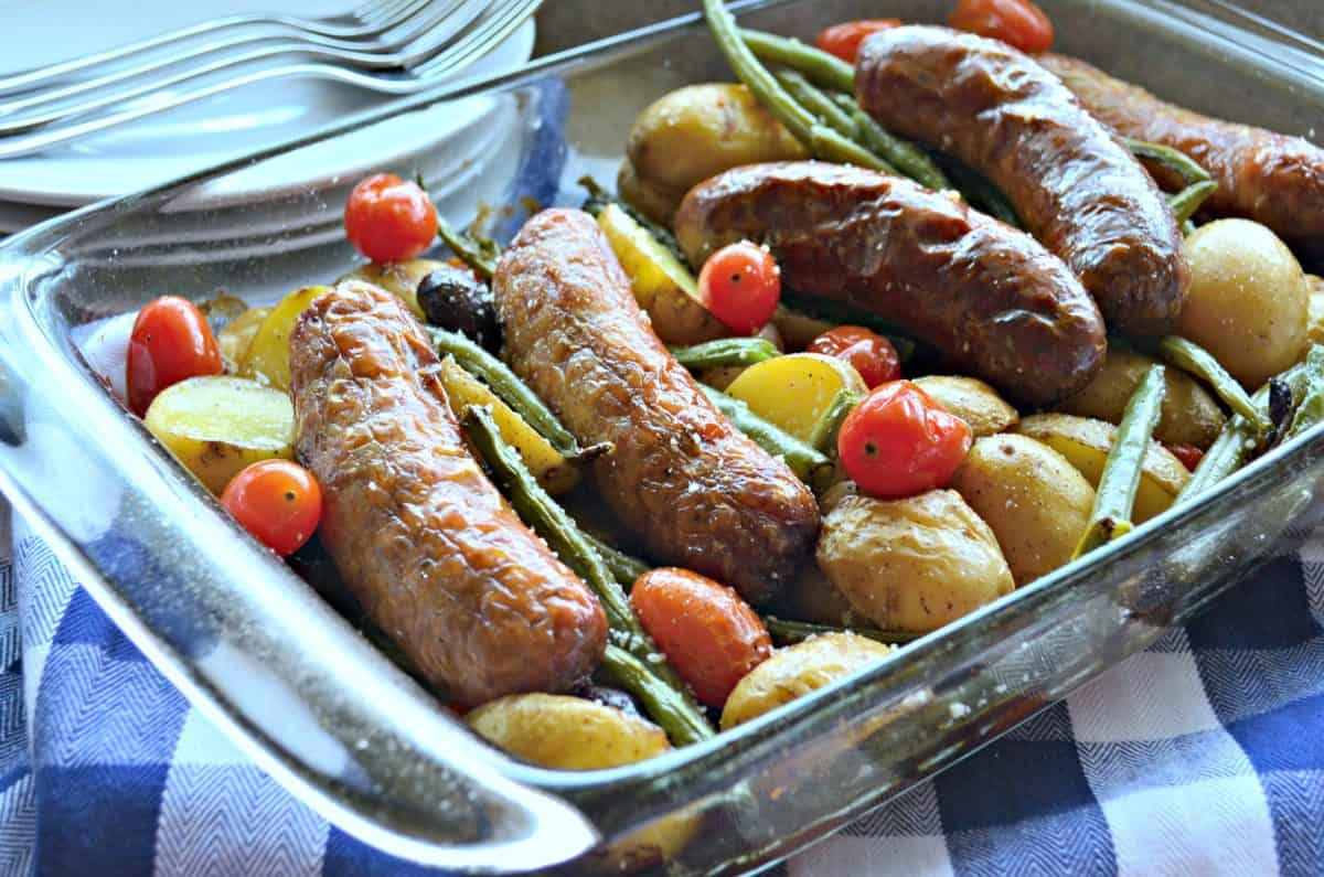 glass casserole dish filled whole sausages, cherry tomatoes, green beans, mini potatoes with seasoning.