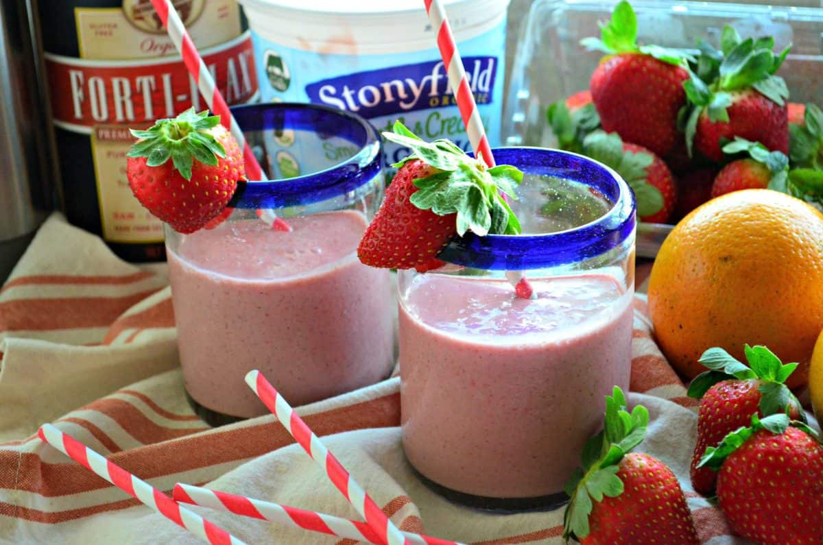 two blue rimmed glasses with red pink blended drink rimmed with fresh strawberries near fresh fruits.