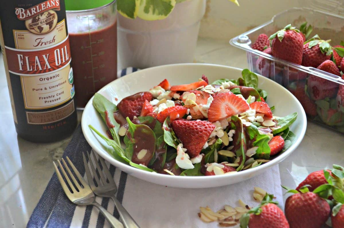 spinach salad with strawberries, almond slivers, dressing, and feta in white bowl next to barlean's flax oil.