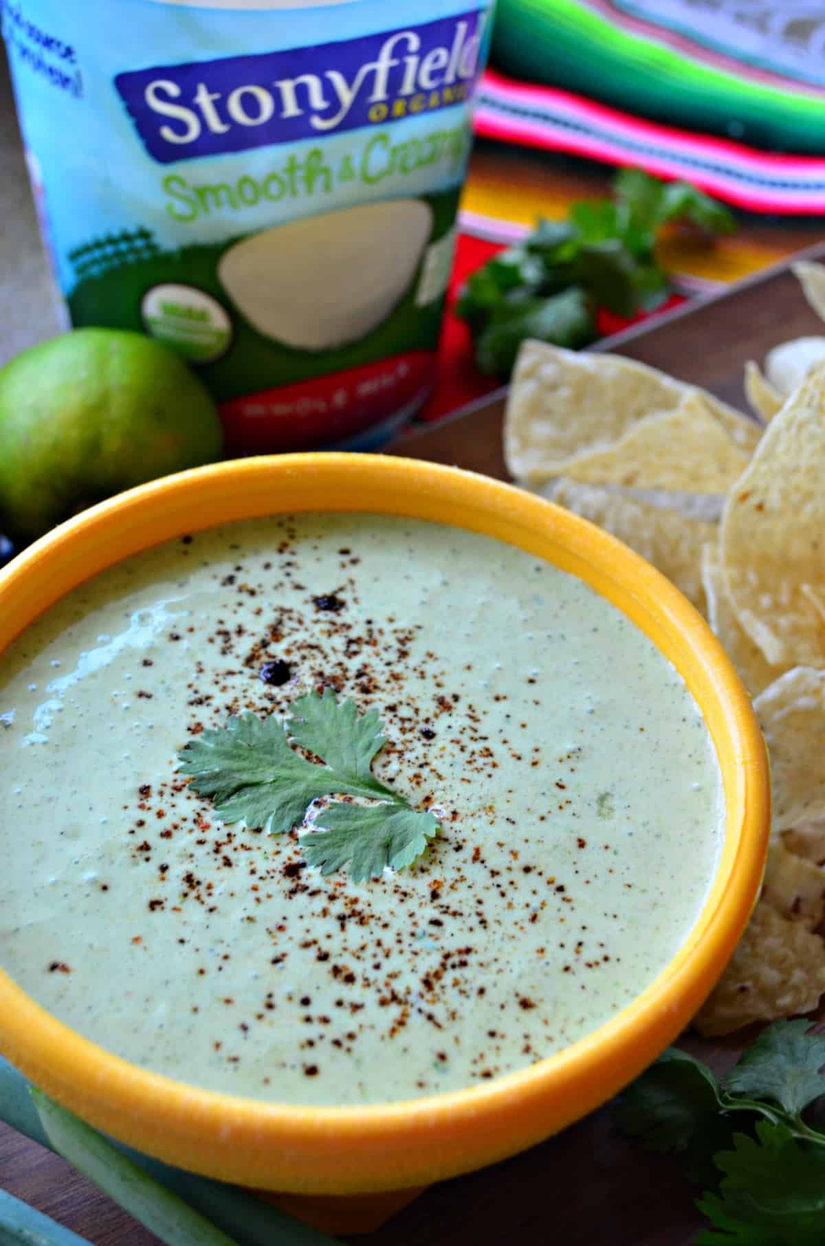 close up top view creamy green dip in yellow bowl topped with cilantro leaf next to corn tortilla chips and limes.