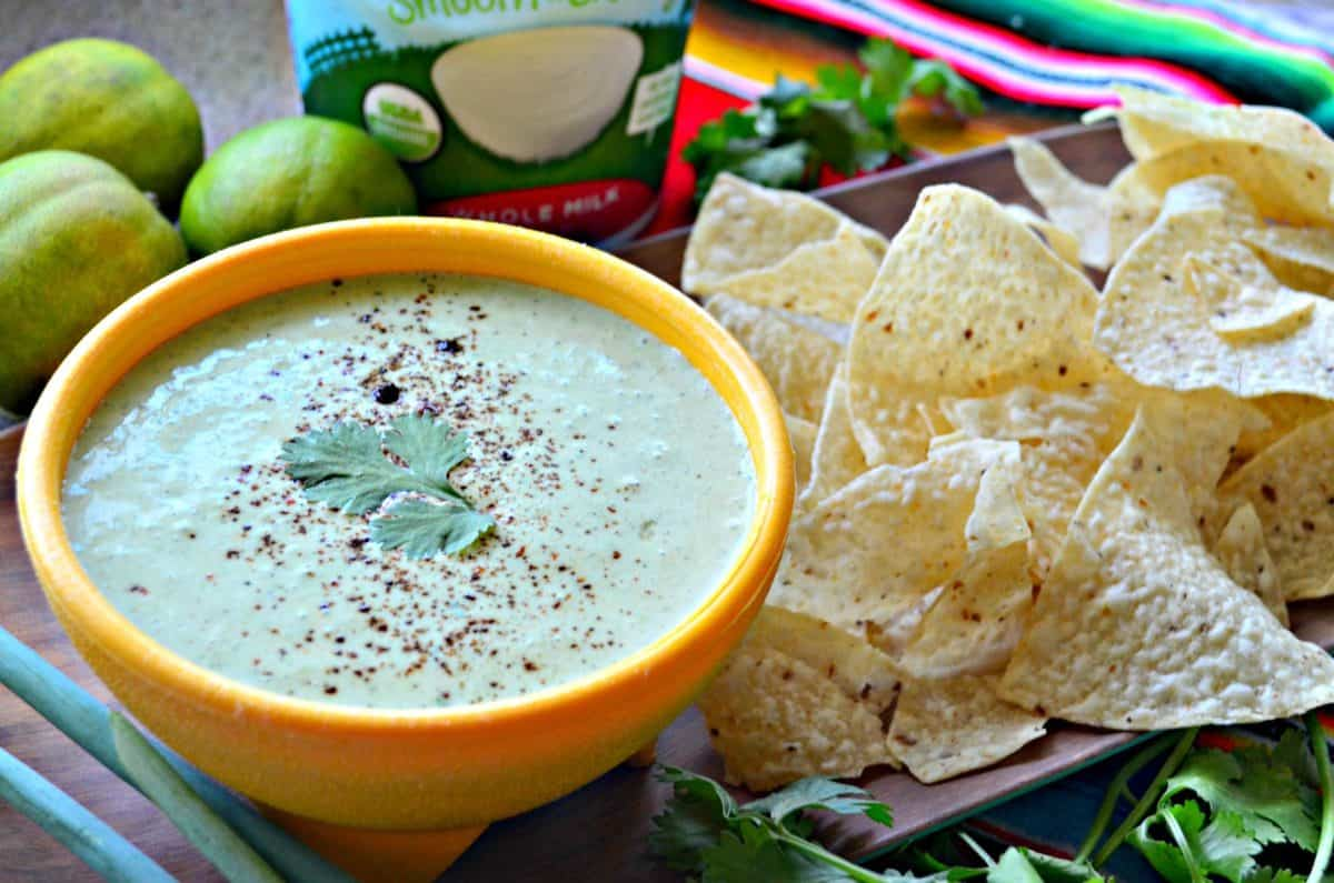 side view of creamy green dip in yellow bowl topped with cilantro leaf next to corn tortilla chips and cilantro.