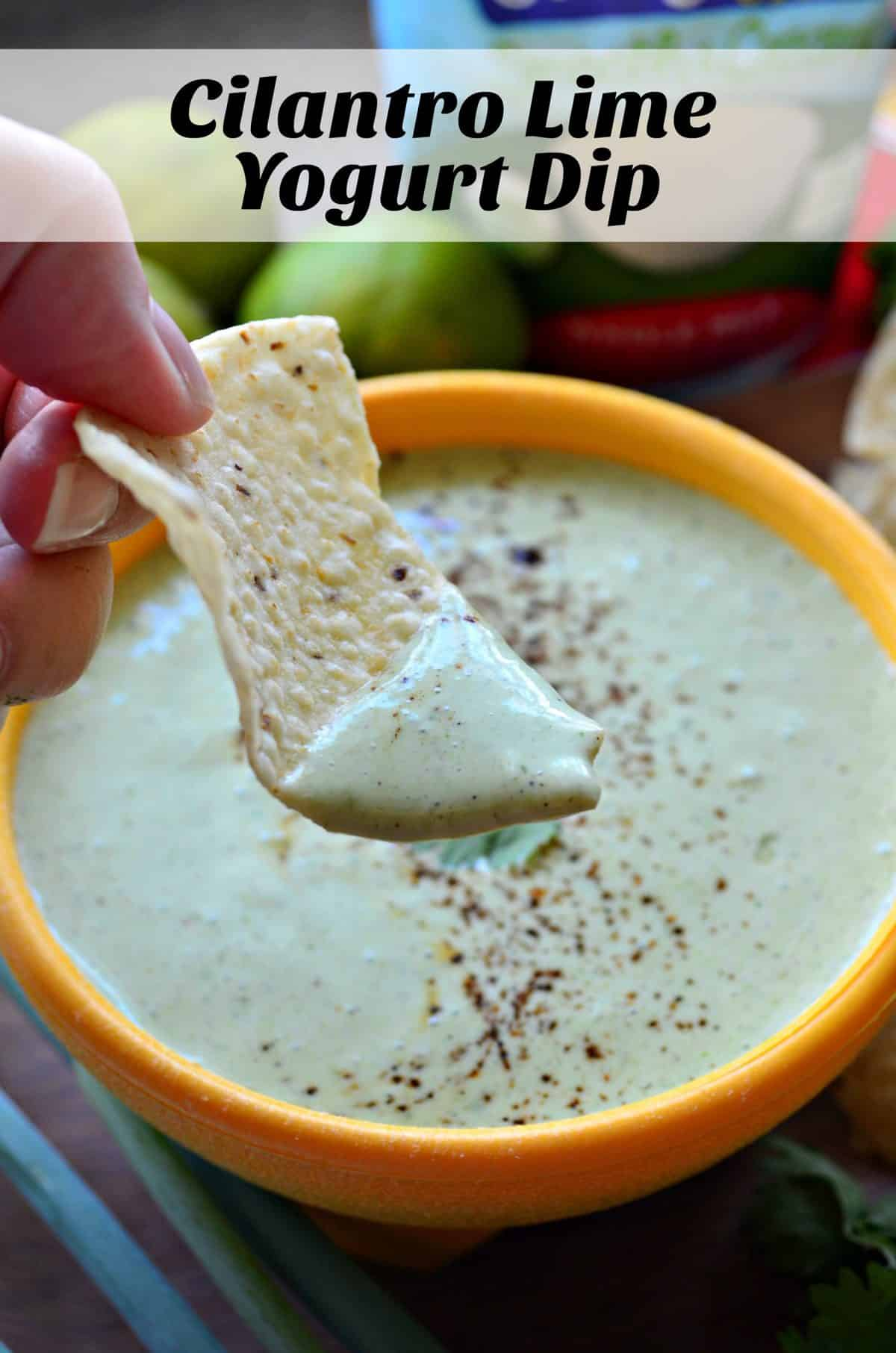 close up of hand dipping corn tortilla chip into Creamy Cilantro Lime Yogurt Dip from yellow bowl with title text.