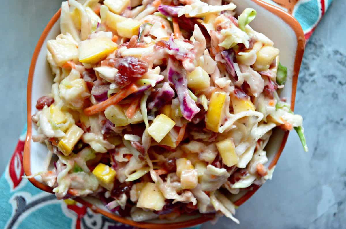 close up top view of shredded carrots, cabbage, and apple slices with sauce in small bowl on counter.