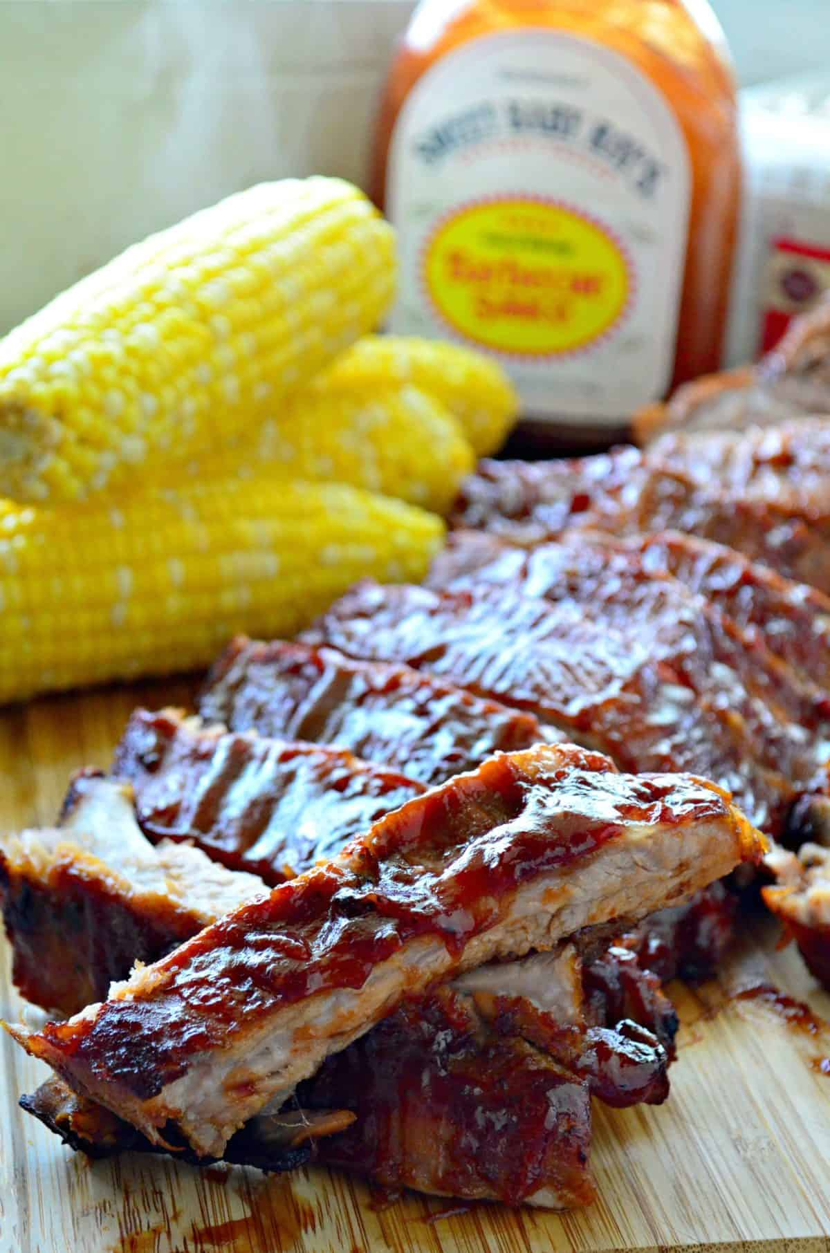 closeup baby back ribs smothered in red sauce and stacked on cutting board in front of fresh corn and BBQ sauce.