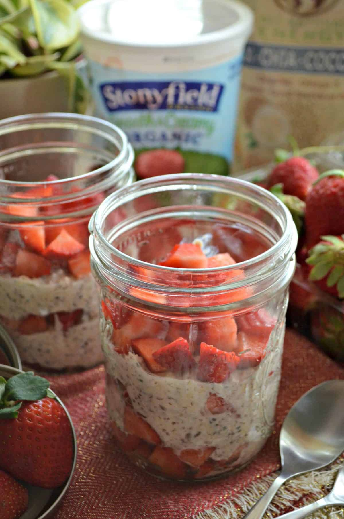 close up top view of small mason jar filled with oatmeal looking substance and chopped strawberries.