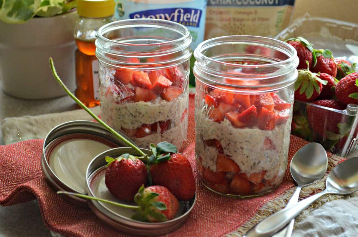 2 small mason jars filled with oatmeal looking substance and fresh chopped strawberries in 3 layers.