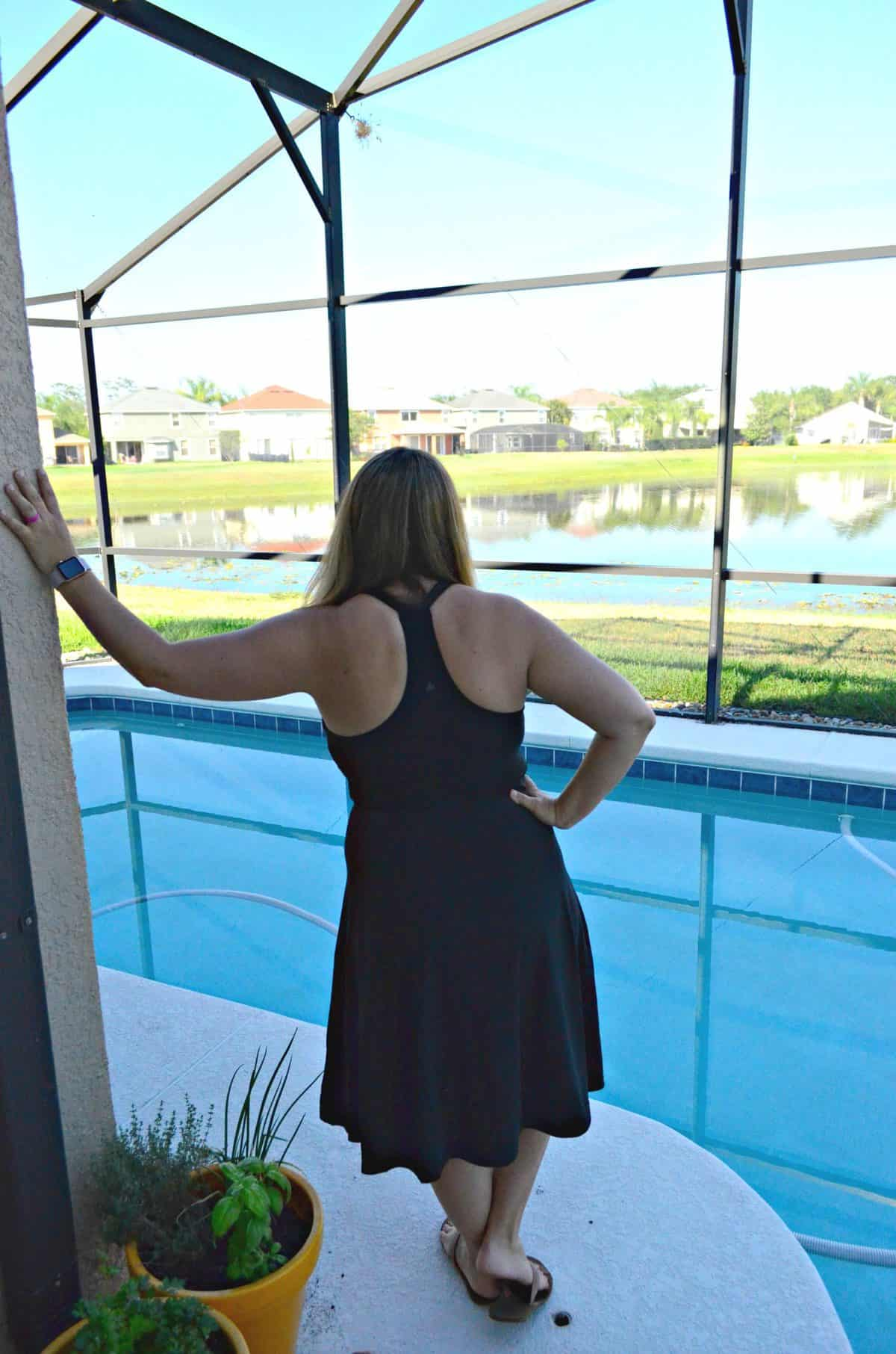 back of woman with brown hair in black prana dress looking at pool.
