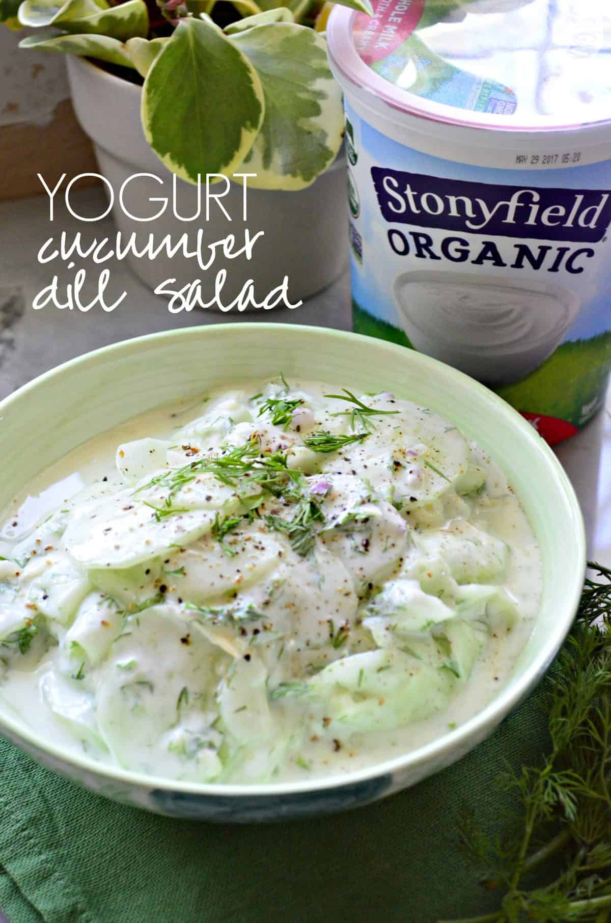 green bowl filled with yogurt dill cucumber salad on countertop in front of stonyfield organic yogurt with title text.
