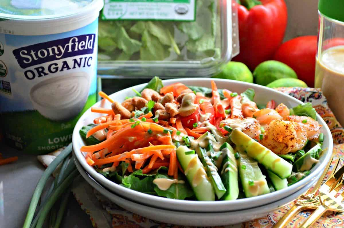 bowl of sliced cucumbers, kale, bell peppers, cashews, carrots, and seasoned shrimp with dressing in front of yogurt.