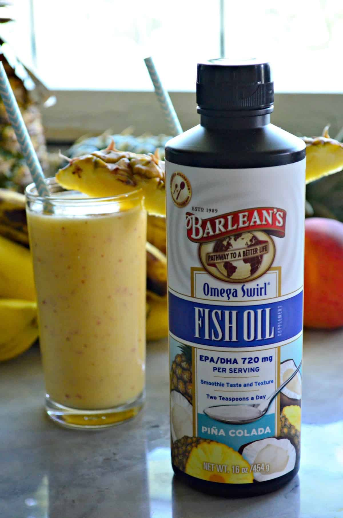 Barleans Fish Oil Omega Swirl Pina Colada Flavor next to glass of yellow smoothie with straw and pineapple slice rim.
