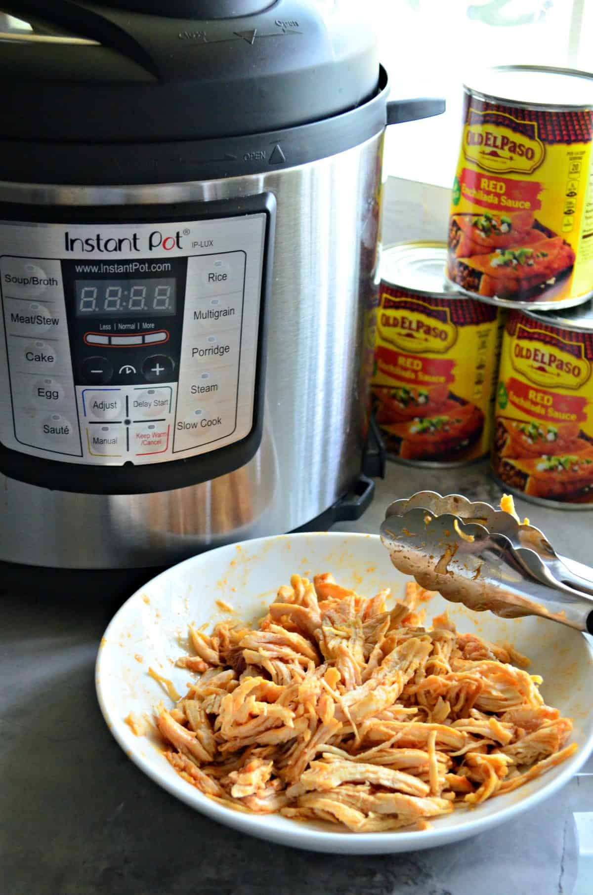 white bowl of shredded chicken with orange/red sauce and tongues on countertop in front of instant pot.