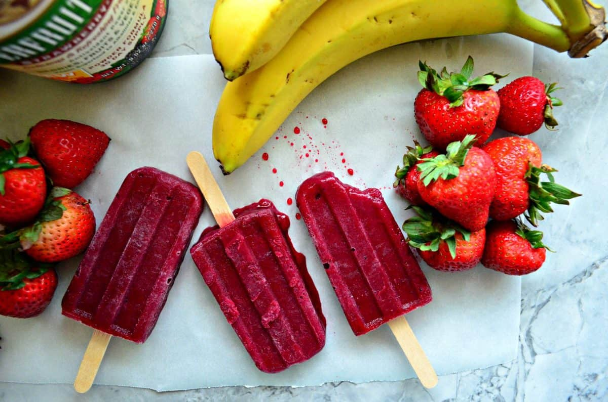 3 beet red popsicles side by side on parchment paper on countertop next to bananas and strawberries.