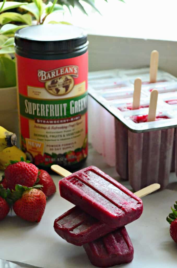 3 beet red popsicles stacked on parchment paper on countertop with popsicle tray in background.