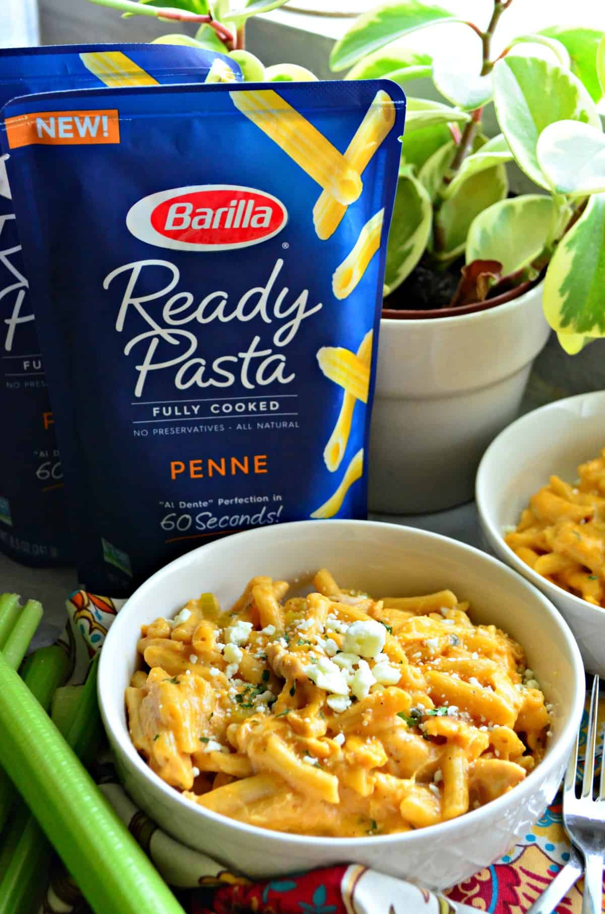 bowl of creamy buffalo chicken pasta next to celery and in front of 2 bags of barilla ready penne pasta.