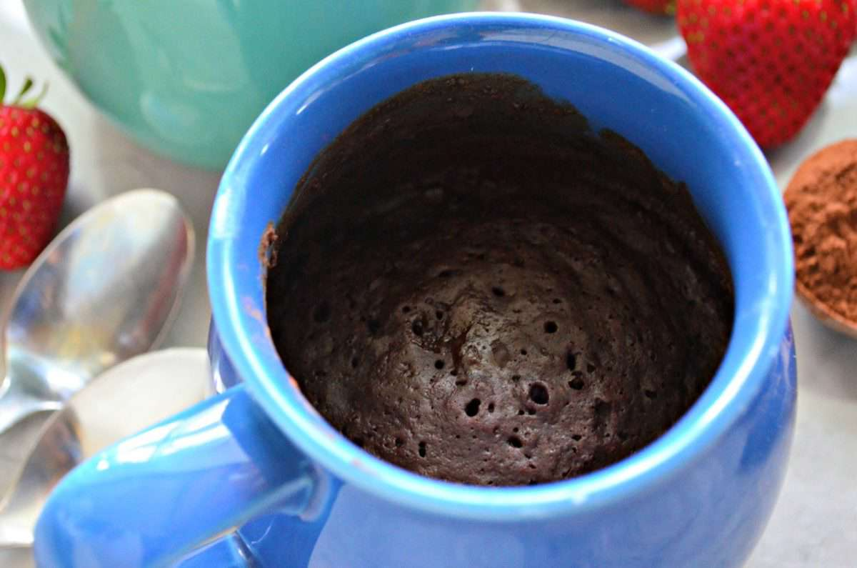 closeup of blue mug filled with brown cake with strawberries blurred in background.