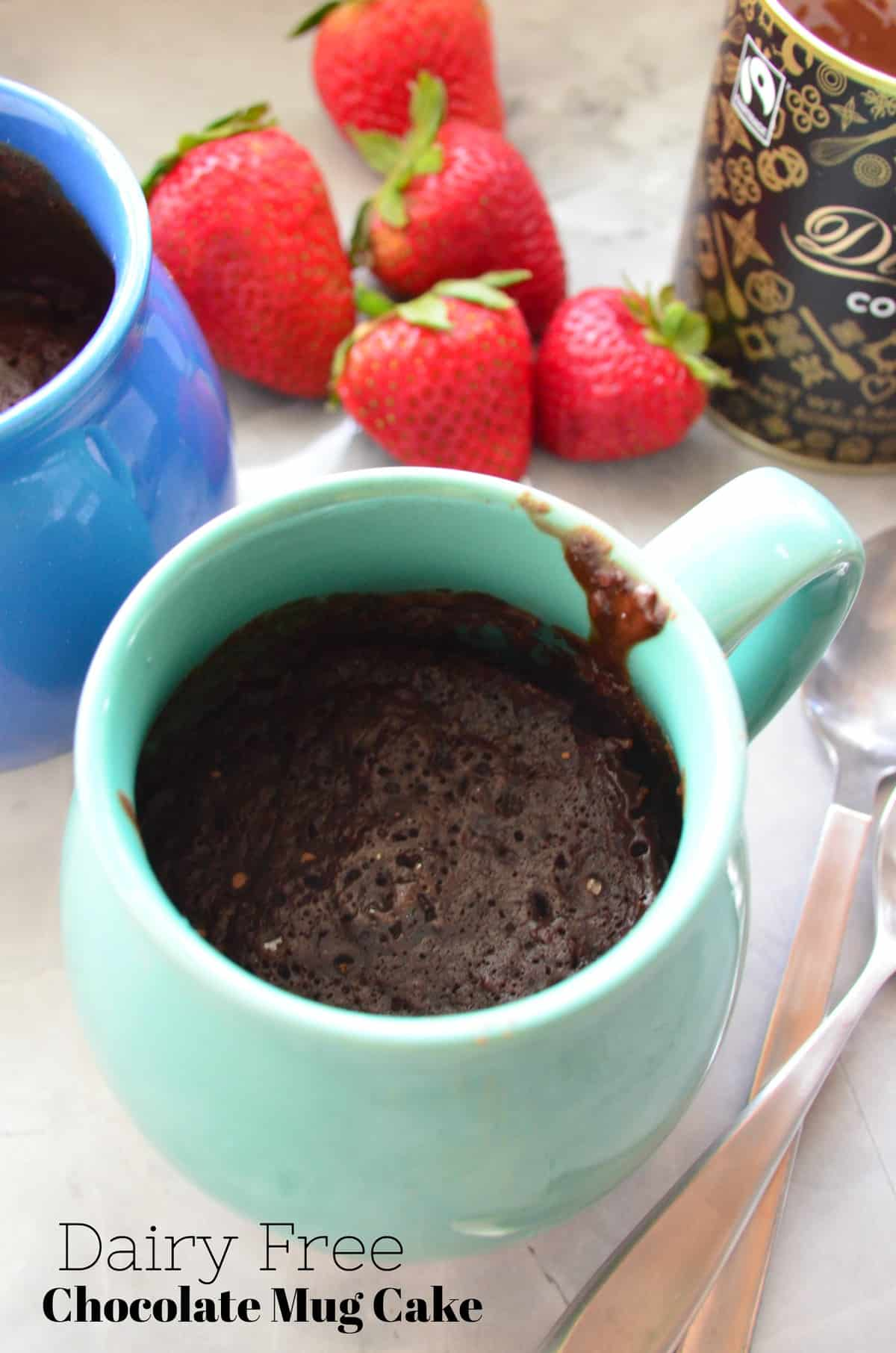 closeup of turquoise mug filled with brown cake with strawberries blurred in background and title text.