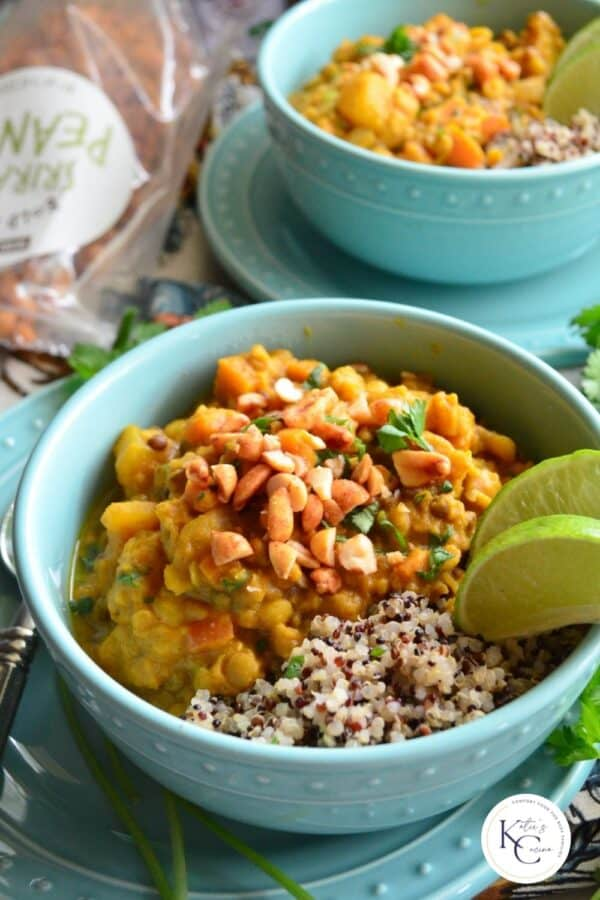 Close up of a teal bowl filled with lentil curry with qunioa and recipe title text on image for Pinterest.
