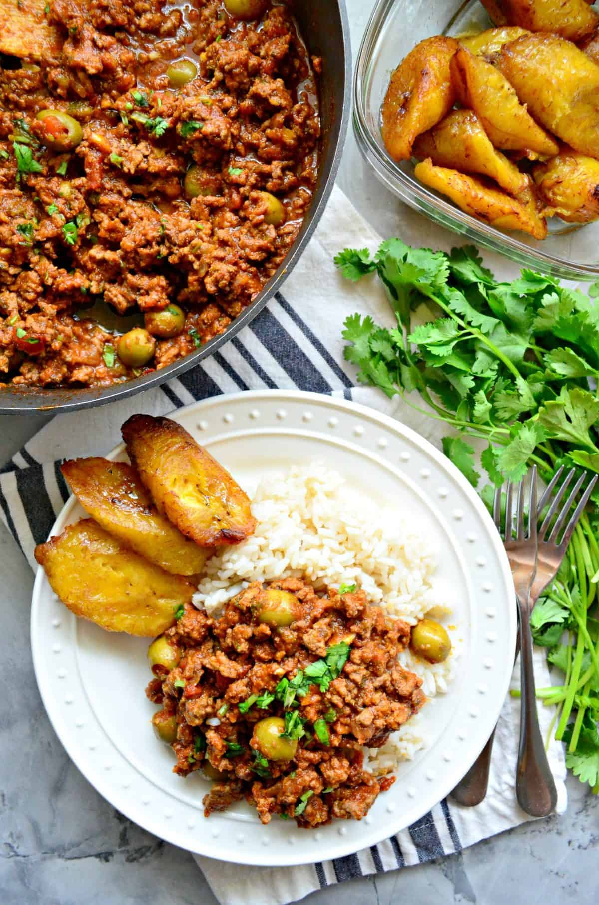 top view plated ground meat, red sauce, green olives, and fresh herbs served with rice and plantains.