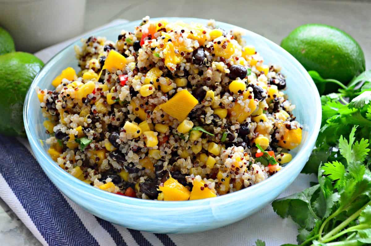 quinoa with corn, peppers, cilantro, and mango in blue bowl next to fresh cilantro and limes.