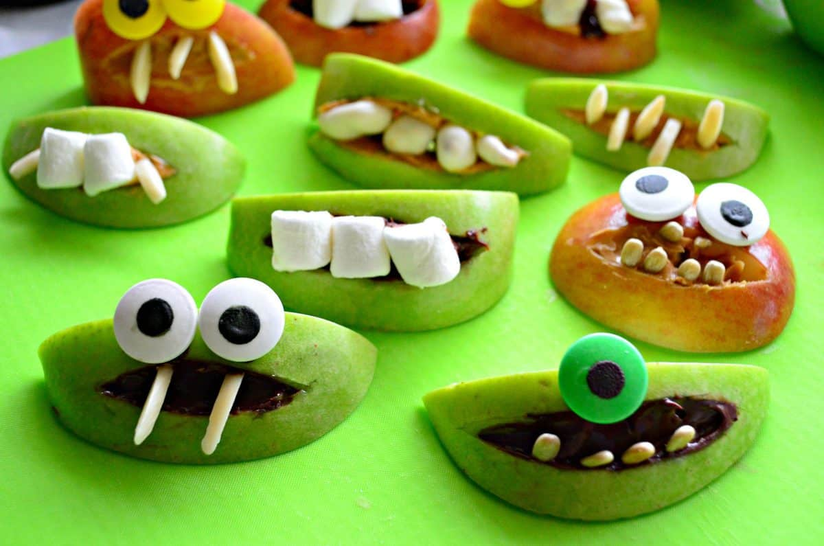 assorted apple slices decorated with peanut butter, nuts, marshmallows, and googly eyes to look like monsters.