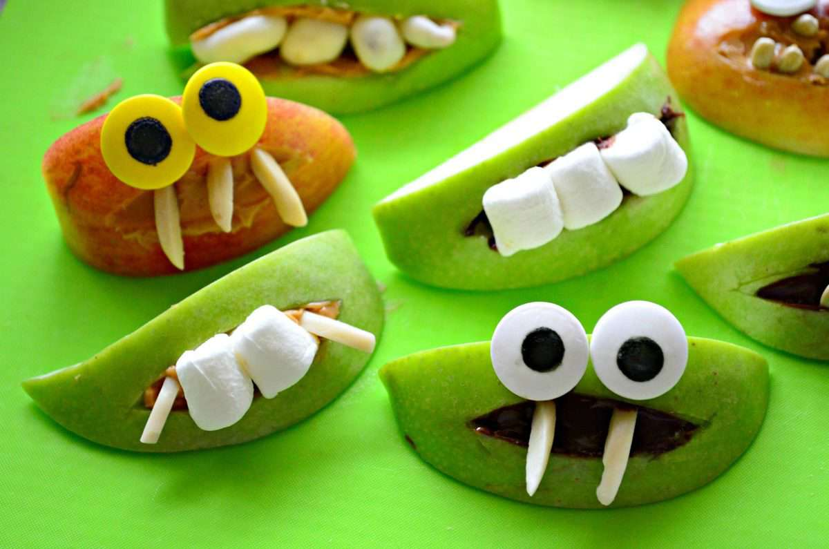 assorted apple slice monsters with marshmallows and nuts for teeth.