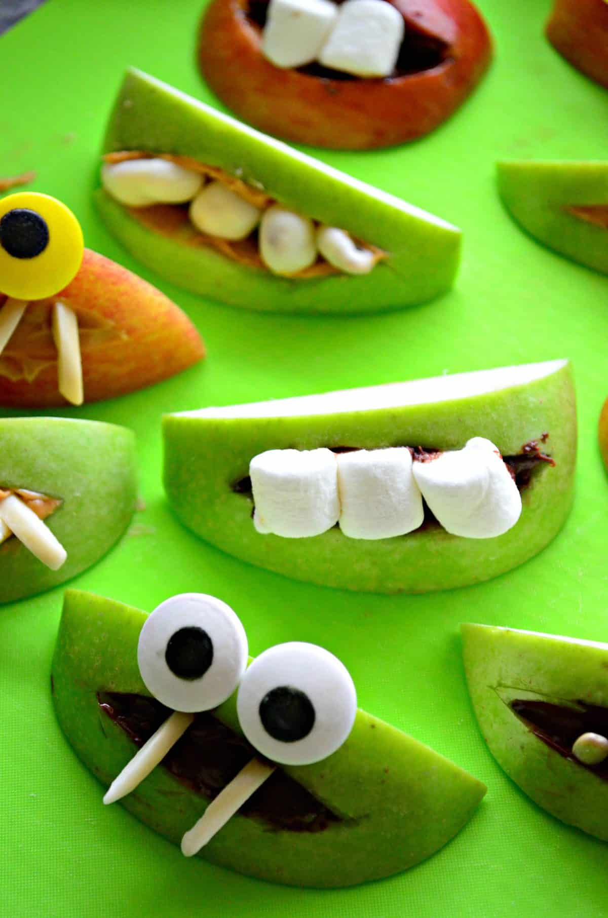 close up of assorted apple slice monsters with marshmallows and nuts for teeth.