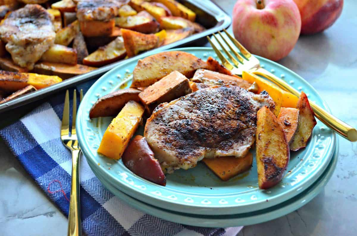 Plated seasoned pork chops, sliced apples, and sliced butternut squash with fork near apples.