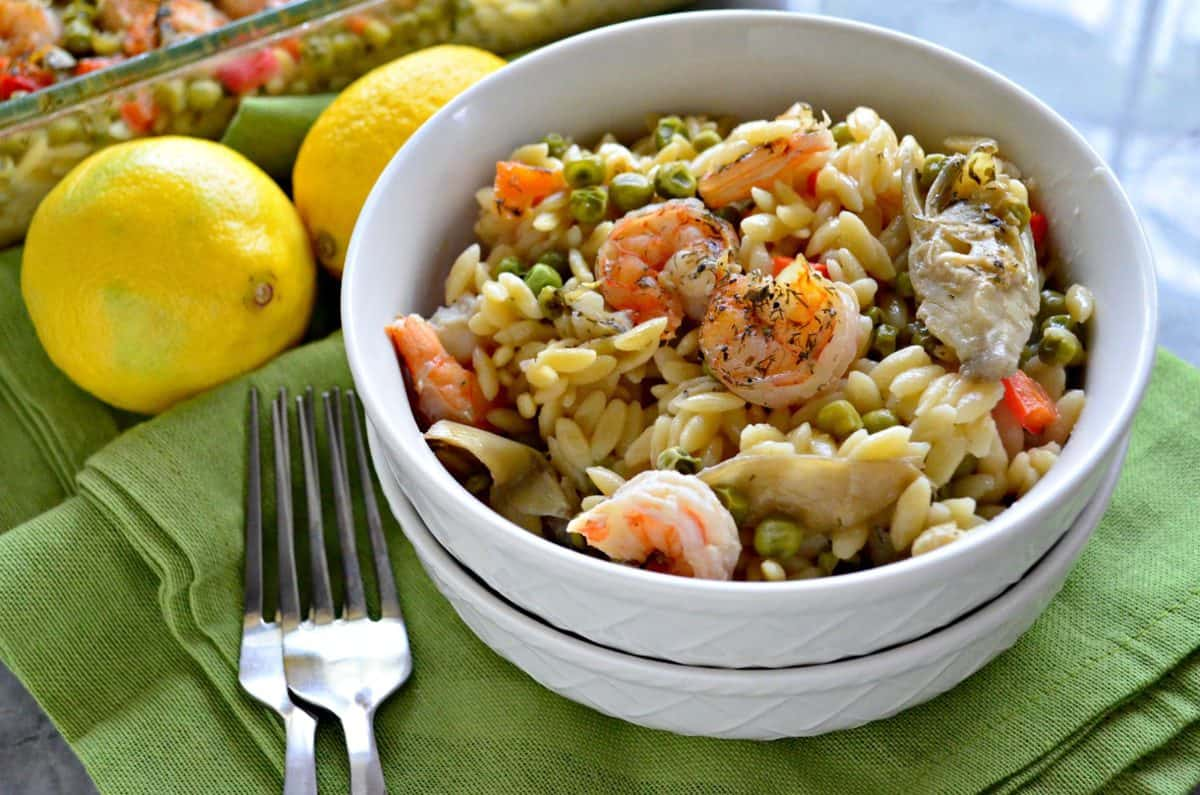 Bowl of shrimp, bell pepper, peas, and orzo on green placemat with forks and fresh whole lemons.