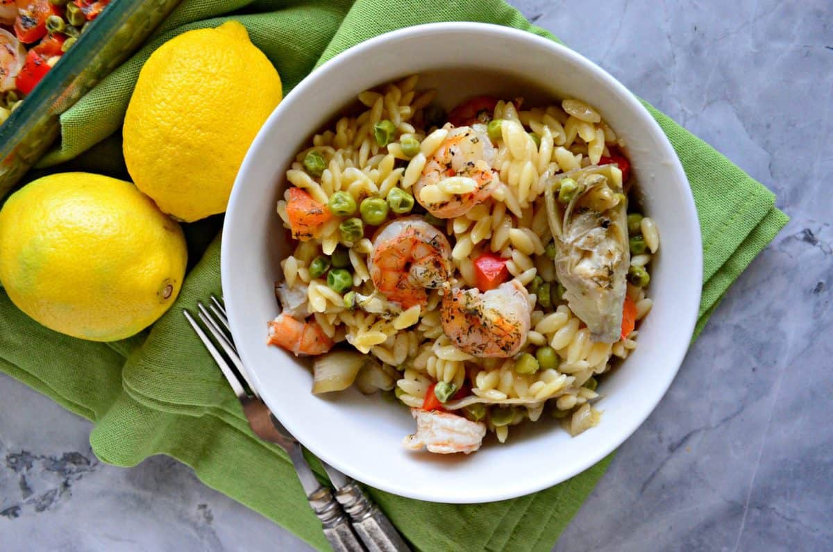 top view of shrimp, bell pepper, peas, and orzo in a white bowl on a green placemat with fresh lemons.