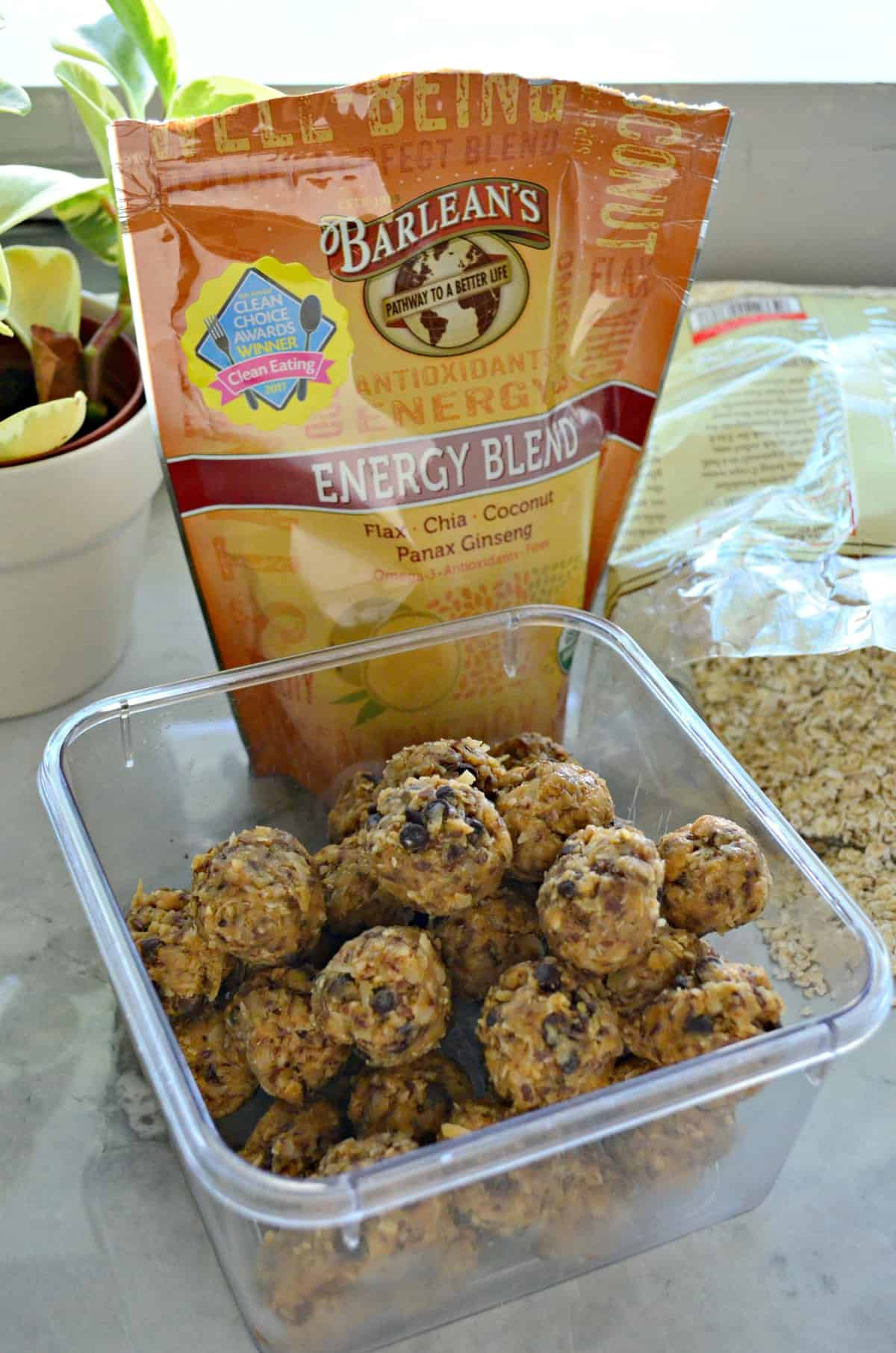 Peanut Butter Chocolate Chip Protein Balls in container on countertop in front of Barlean's Energy Blend.
