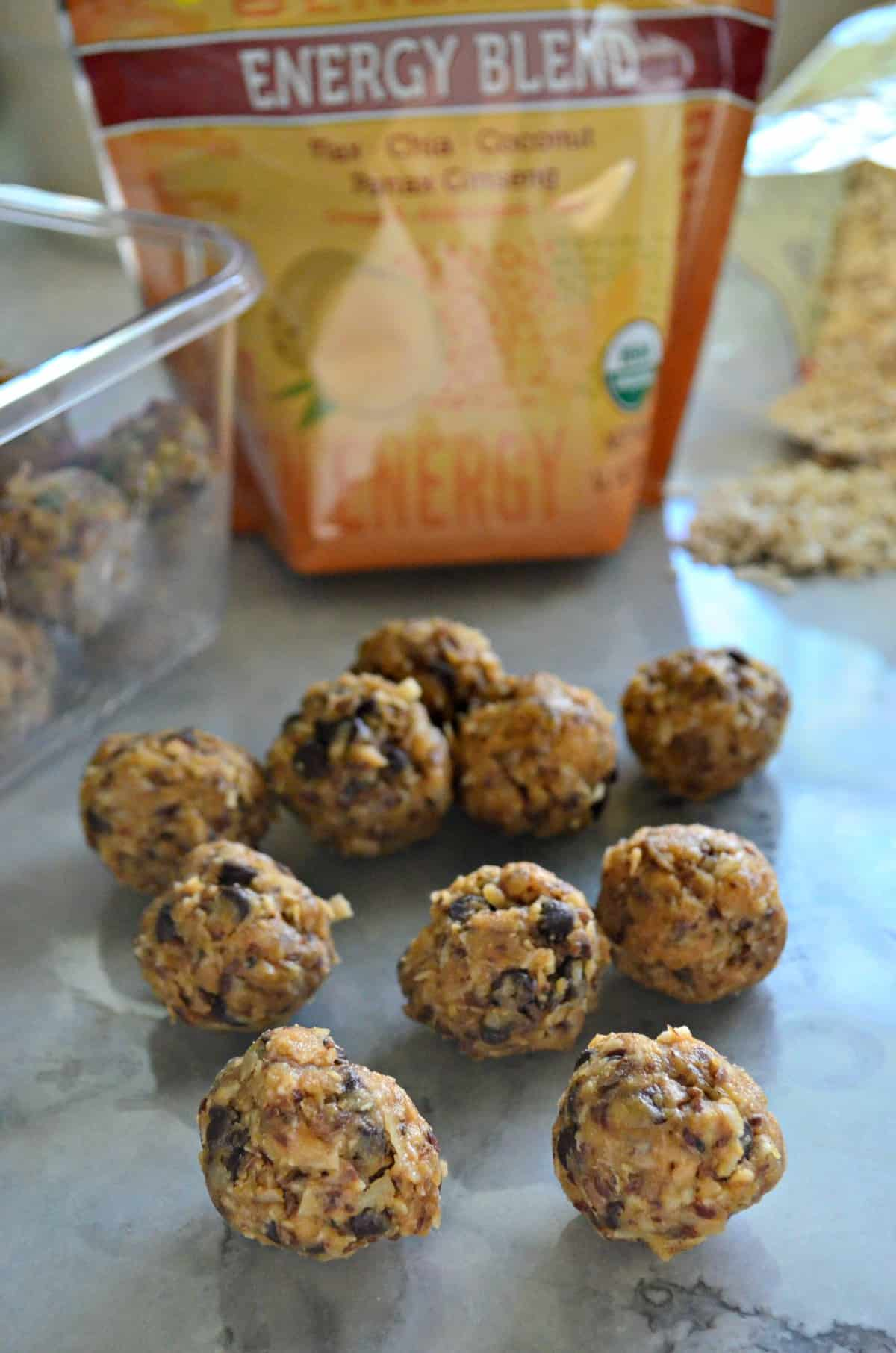 Peanut Butter Chocolate Chip Protein Balls on countertop in front of ingredients and tupperware with title text.