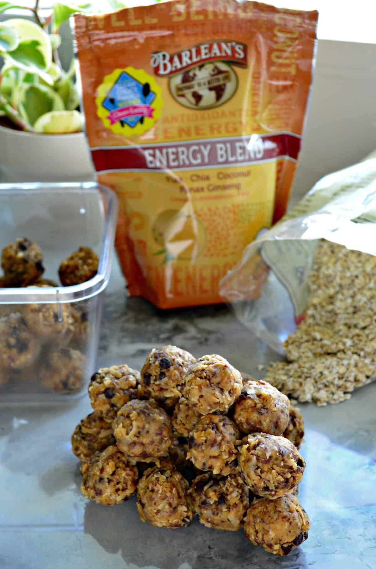 Peanut Butter Chocolate Chip Protein Balls stacked on countertop in front of ingredients and tupperware.