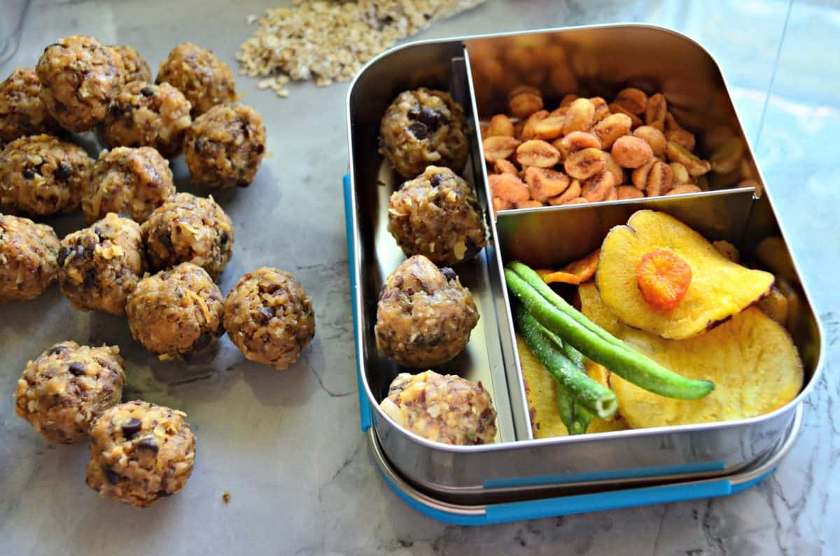 Peanut Butter Chocolate Chip Protein Balls on countertop next to lunch container with nuts and veggies.
