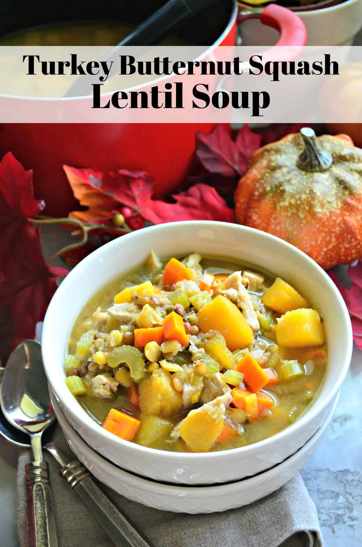 Turkey Butternut Squash and Lentil Soup in white bowl on table with fake decorative fall leaves and title text.