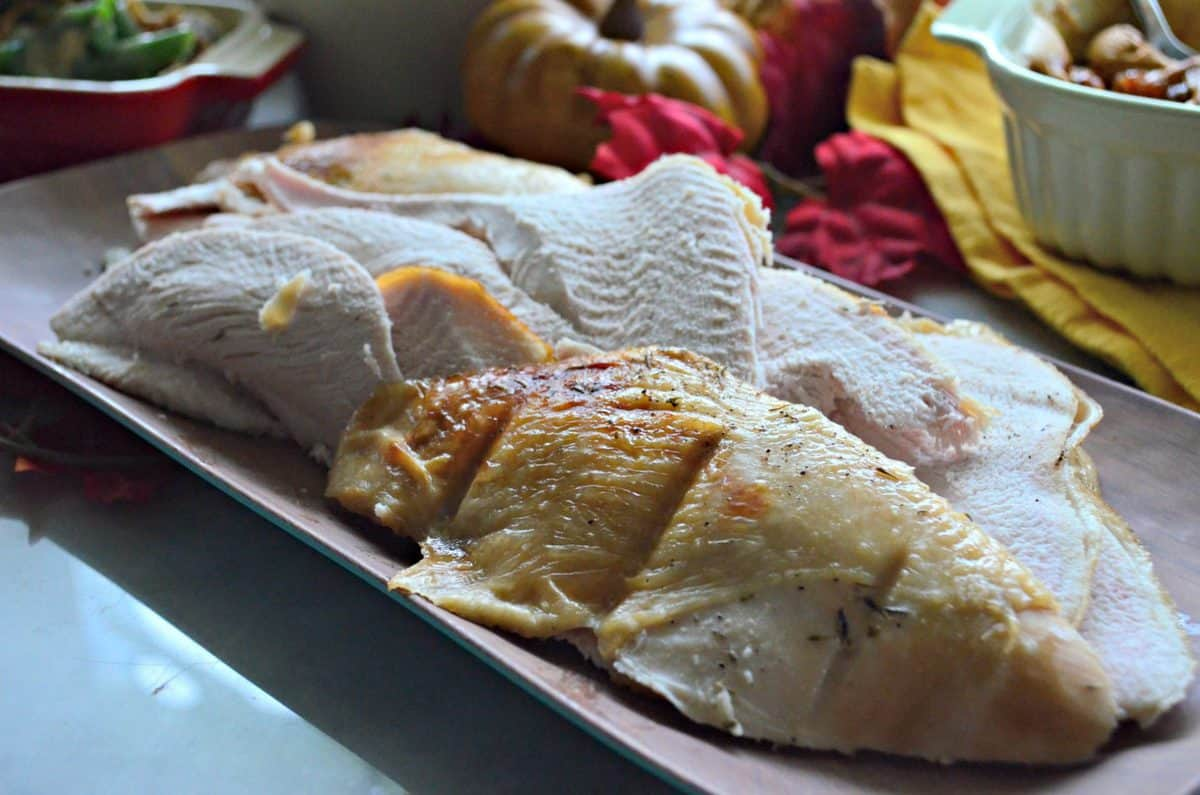 side view of sliced and cooked Garlic & Thyme Turkey Breast on rectangular platter in front of fall decor.