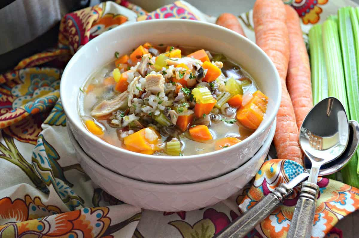 soup in a white bowl with broth, celery, carrots, rice, herbs, and turkey on a tablecloth.