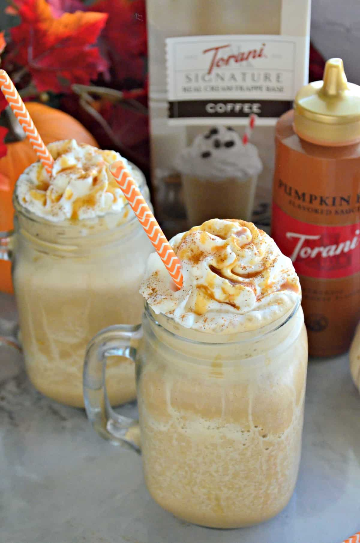 2 mason jar glass mugs with handle filled with frozen drink topped with whipped cream and caramel.