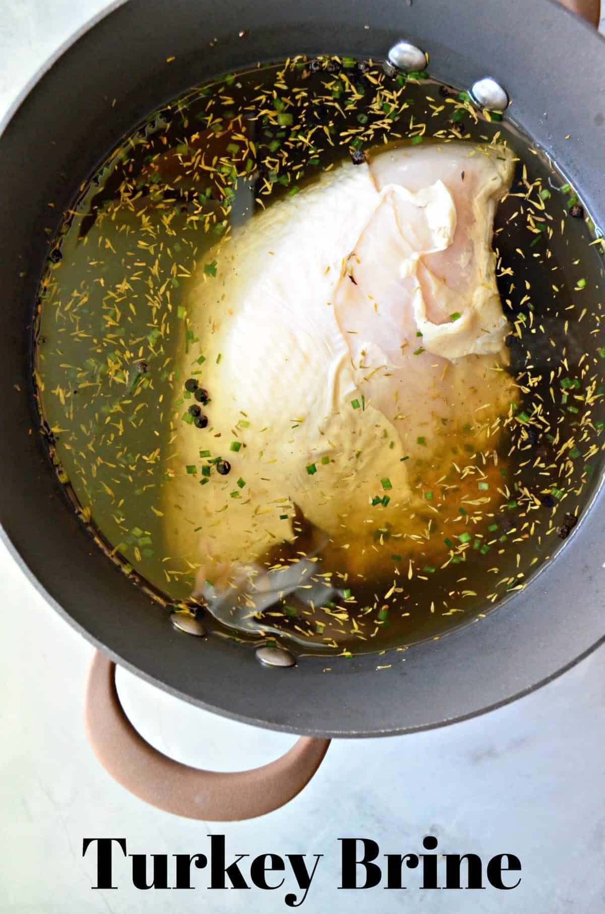 top view of raw Turkey brining in yellowish liquid with herbs in pot with title text.