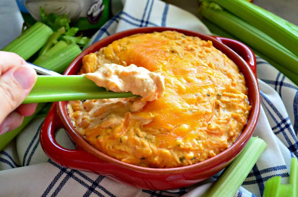 hand dipping piece of celery into thick orange cheesy dip in red bowl.