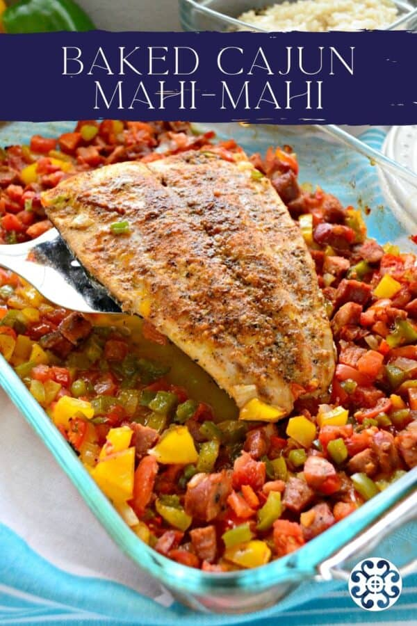 Silver spatula holding a mahi filet with peppers and sausage with text on image for Pinterest.