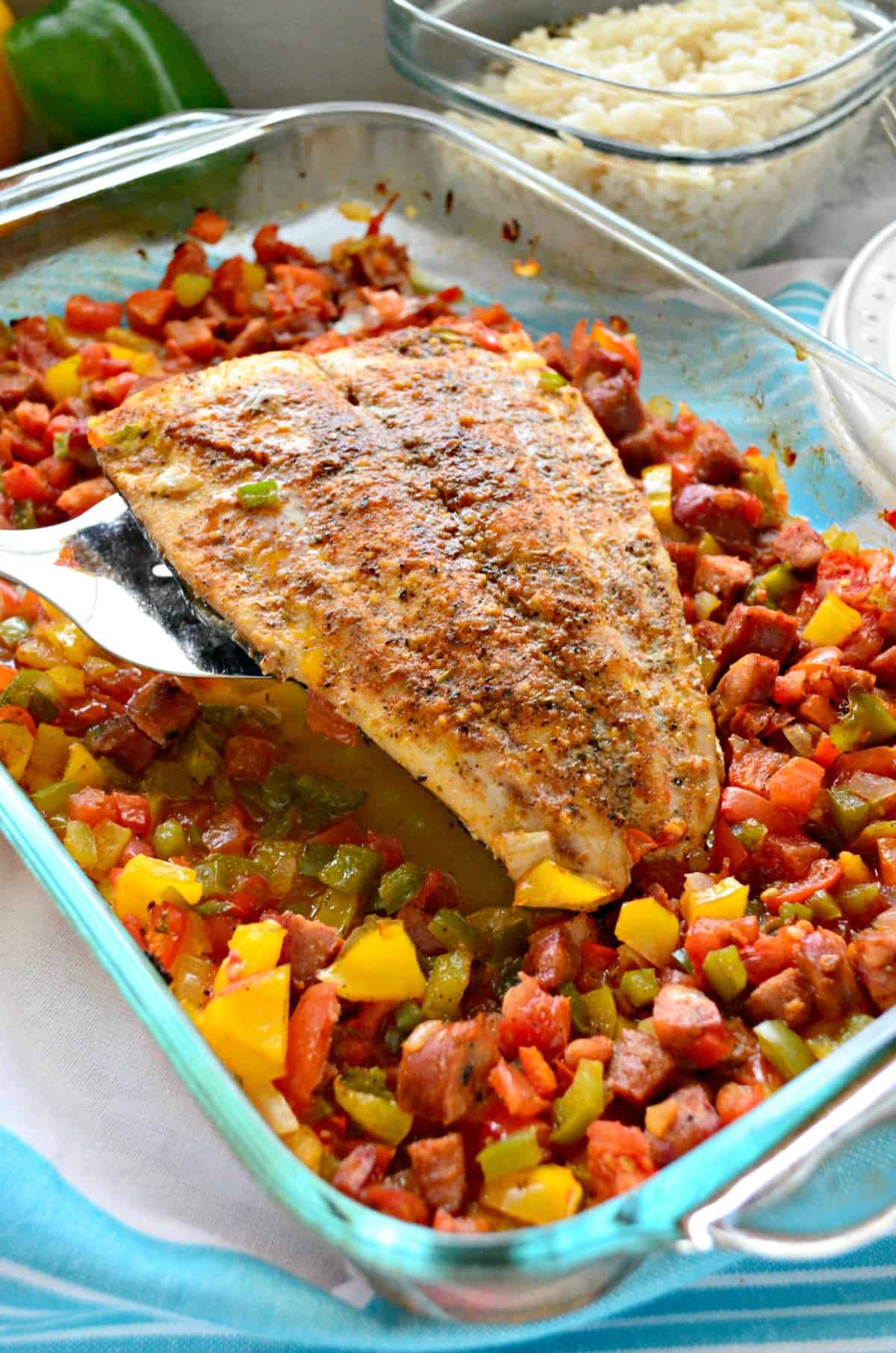 whole baked mahi mahi held up with spatula over chopped veggies and sausage in glass baking dish.