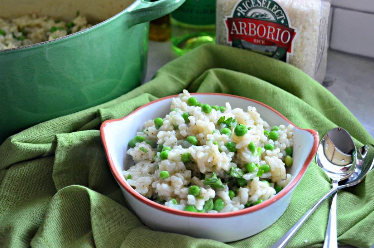 Baked Risotto with Green Peas and pepper in small white bowl on green tablecloth with two spoons.