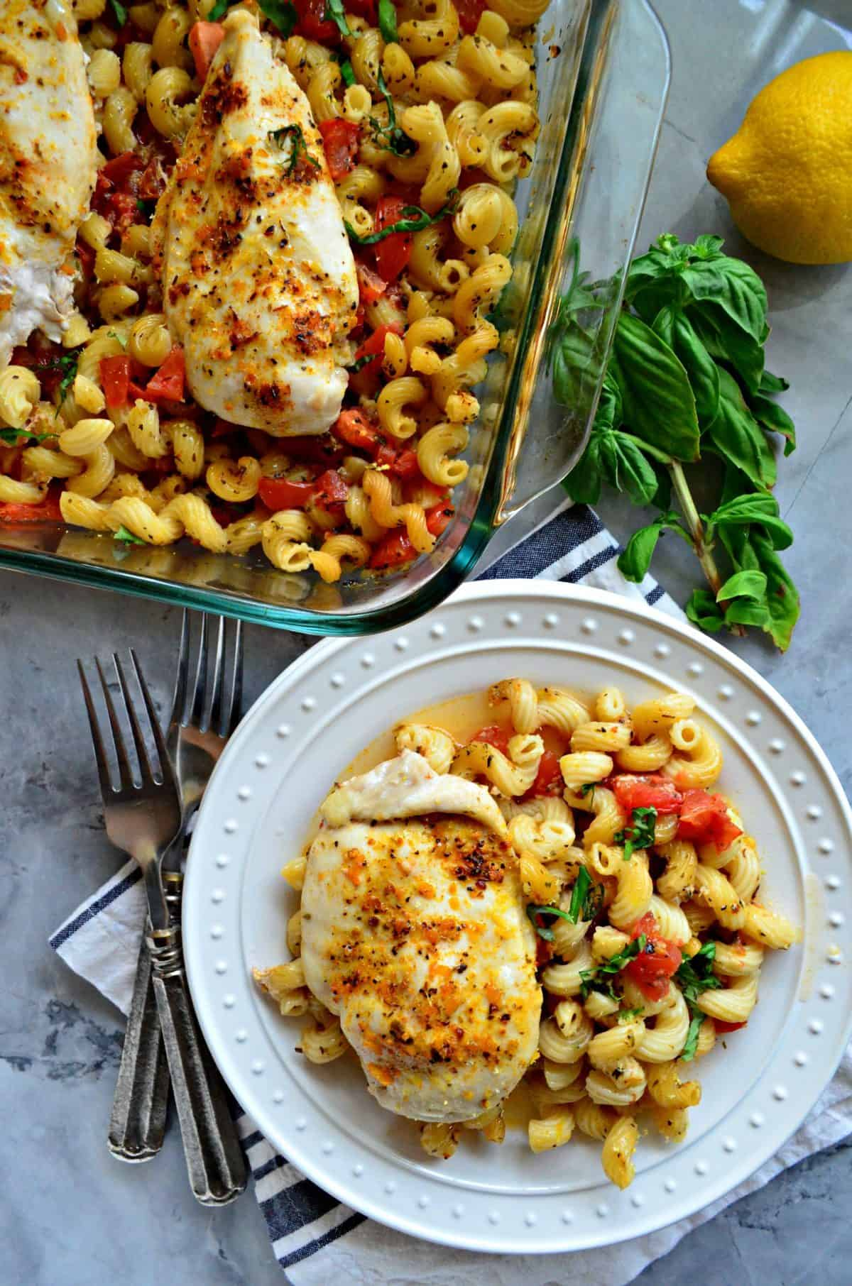 plated chicken breast and cavatapi with herbs and tomatoes next to baking dish of leftovers.