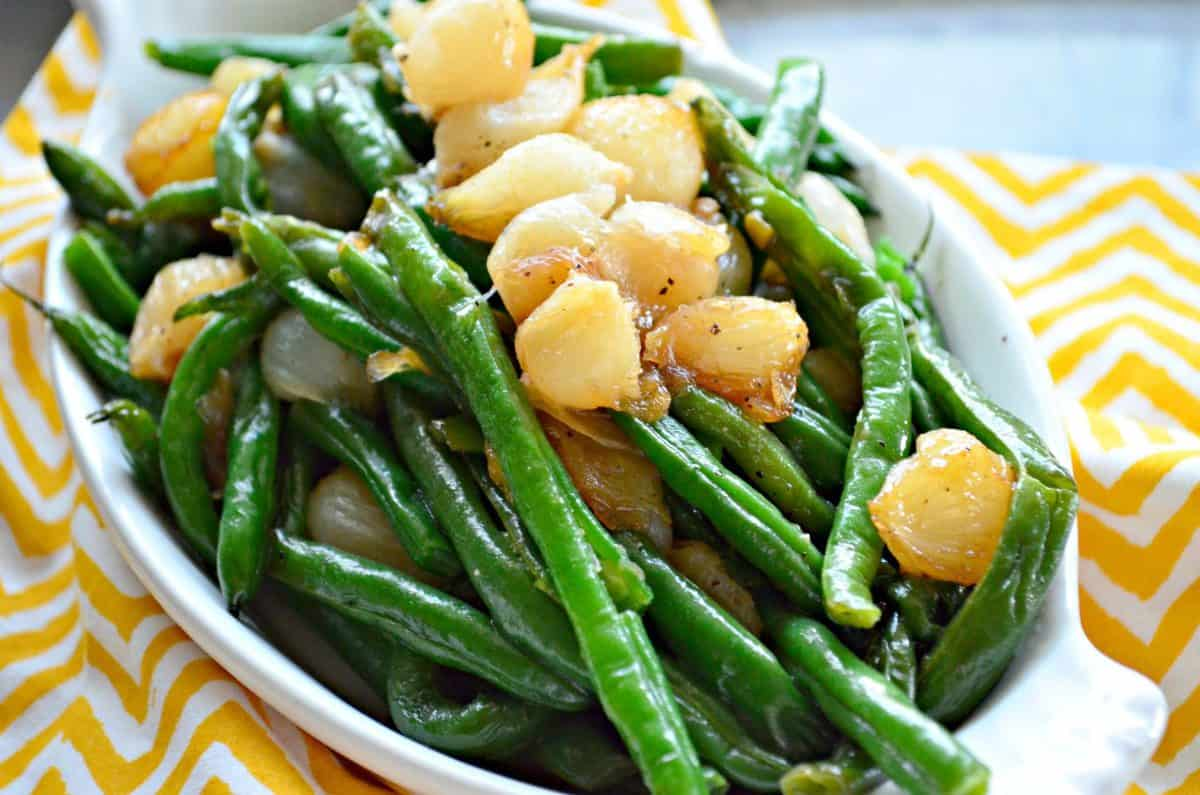 Green Beans with Caramelized Pearl Onions in oval ceramic dish on yellow and white chevron tablecloth.