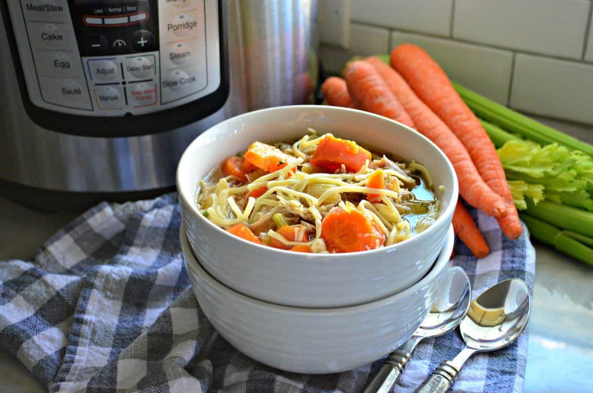 bowl of chicken noodle soup with carrots and celery in it in front of instant pot, carrots, and celery.